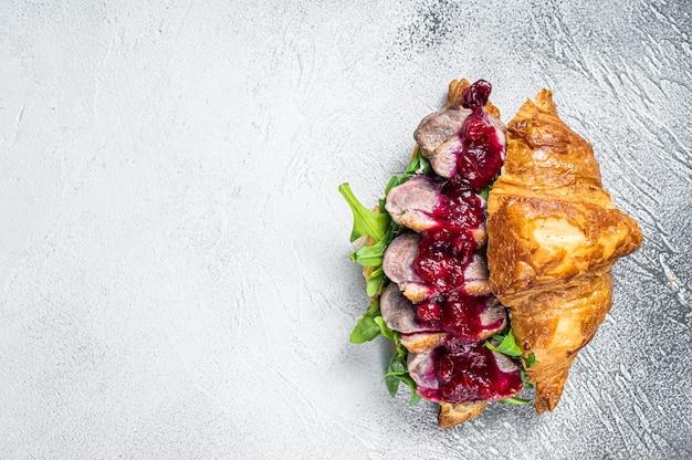 Sanduíche de croissant de peito de pato com fatias de bife, rúcula e molho