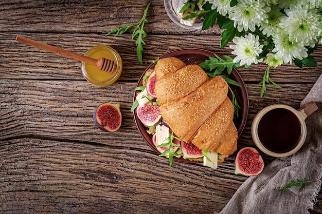 Sanduíche de croissant fresco com rúcula de queijo brie e figos. delicioso café da manhã. comida saborosa. postura plana. vista do topo