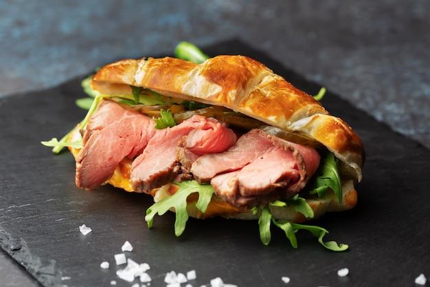 Sanduíche de croissant recém-assado com rúcula e rosbife em uma placa de ardósia preta