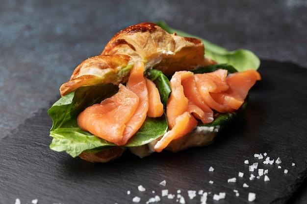 Sanduíche de croissant recém-assado com salada e salmão em uma placa de ardósia preta