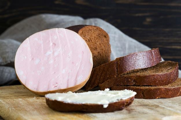Sanduíche de farinha de centeio amargo com manteiga e linguiça cozida com banha, sanduíches caseiros na europa oriental, closeup de comida