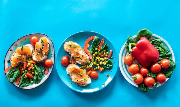 Sanduíche de fotocomposição de café da manhã com ervas de salmão e vegetais na parte superior do fundo v