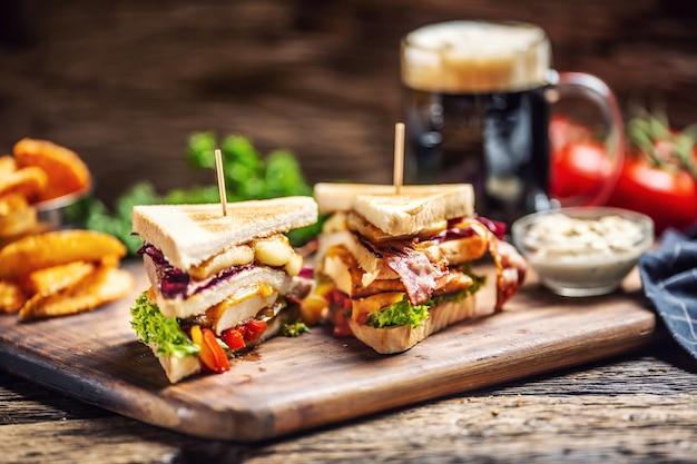 Sanduíche de frango e queijo com bacon, repolho roxo, pimentão e salada com uma cerveja escura ao fundo.