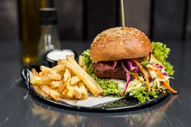 Sanduíche de frango frito com legumes e batatas fritas em uma mesa de madeira