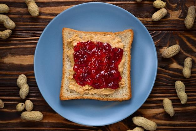 Sanduíche de geleia e manteiga de amendoim em fundo de madeira.