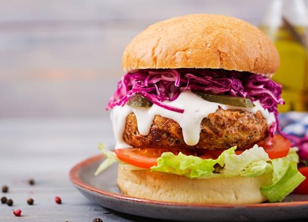 Sanduíche de hambúrguer com hambúrgueres suculentos, tomate e repolho roxo