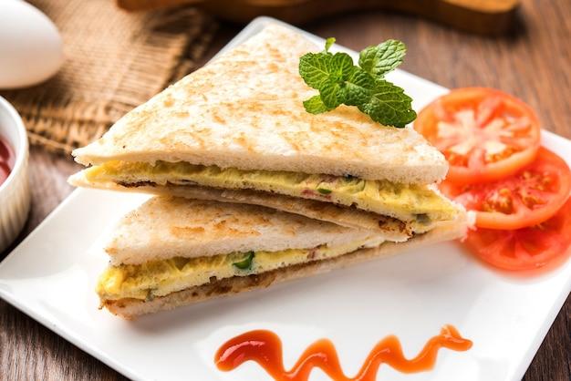 Sanduíche de omelete de pão indiano ou omelete servido com ketchup de tomate. med para cima de ovo de galinha. servido sobre fundo temperamental. foco seletivo