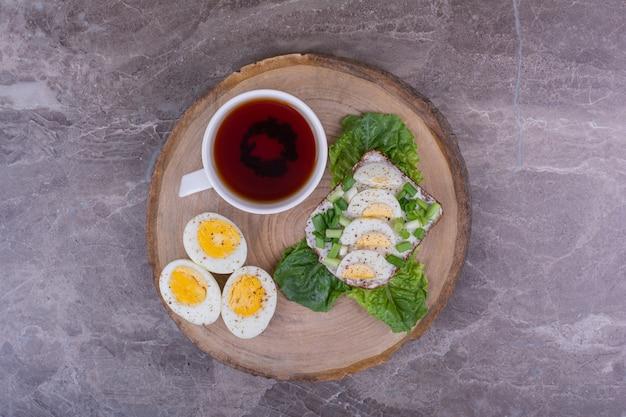 Sanduíche de ovo com ervas e uma xícara de chá