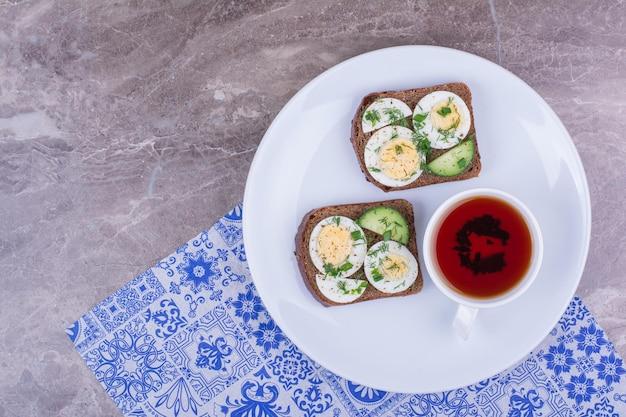 Sanduíche de ovo cozido com uma xícara de chá em um prato branco.