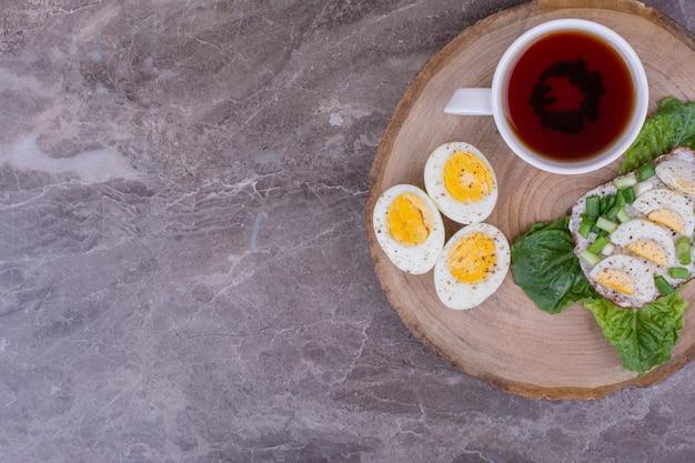Sanduíche de ovo cozido com uma xícara de chá em uma placa de madeira.