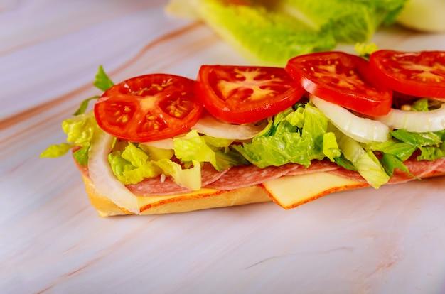 Sanduíche de pão ciabatta com salame, queijo e vegetais.