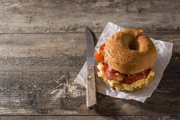 Sanduíche de pão com bacon, ovo e queijo na mesa de madeira