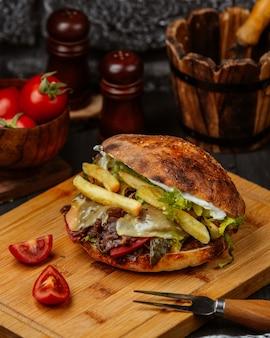 Sanduíche de pão com carne, batatas fritas e legumes.