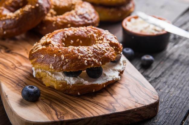 Sanduíche de pão com creme de queijo e mirtilo na mesa de madeira