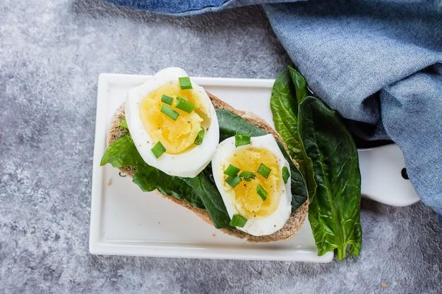 Sanduíche de pão com espinafre e ovos cozidos na placa cerâmica no fundo da mesa cinza, vista superior