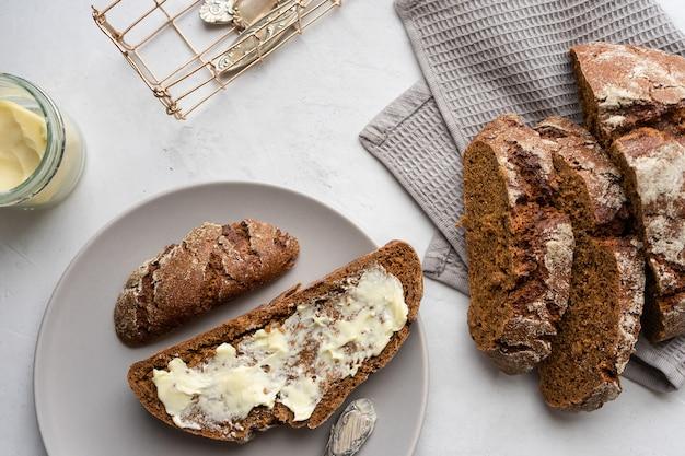 Sanduíche de pão com manteiga em um fundo cinza.