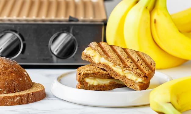 Sanduíche de pão de centeio grelhado com banana e cream cheese