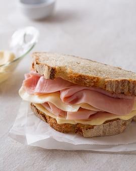 Sanduíche de pão de massa fermentada de presunto e queijo em papel manteiga