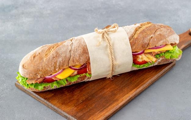 Sanduíche de pão escuro com salada, bacon, tomate, queijo e cebola. café da manhã. comida rápida.