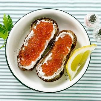 Sanduíche de pão fresco com caviar vermelho e queijo em um prato. combinação clássica de ingredientes. lanche na mesa