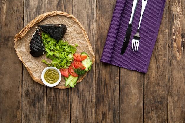 Sanduíche de pão preto com legumes em uma superfície de madeira