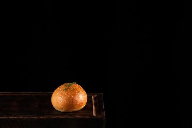 Sanduíche de pão redondo em quadro escuro com espaço de cópia