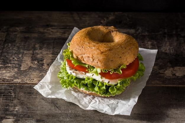 Sanduíche de pão vegetal com tomate, alface e queijo mussarela na mesa de madeira.