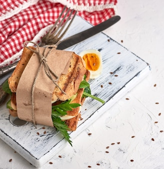 Sanduíche de pedaços quadrados de pão torrado, legumes e ovos cozidos