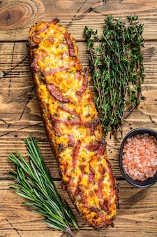 Sanduíche de pizza no pão baguete com presunto, bacon, legumes e queijo na mesa de madeira