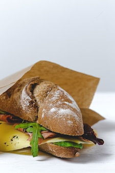 Sanduíche de presunto caseiro com rúcula, alface e queijo com pão de semente. remover. entrega de comida