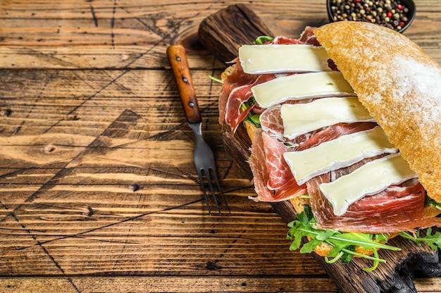 Sanduíche de presunto de parma no pão ciabatta com rúcula e queijo brie de camembert. fundo de madeira. vista do topo. copie o espaço.