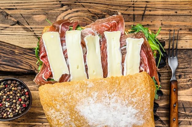 Sanduíche de presunto de parma no pão ciabatta com rúcula e queijo brie de camembert. fundo de madeira. vista do topo.