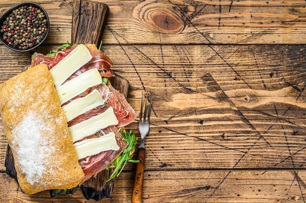Sanduíche de presunto de parma no pão ciabatta com rúcula e queijo brie de camembert.