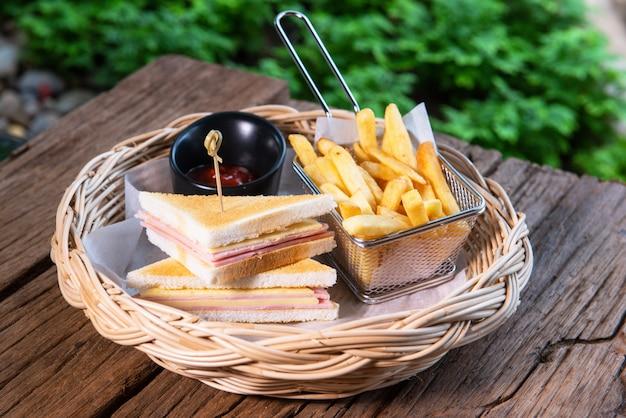 Sanduíche de presunto e queijo, servido com batatas fritas e molho de tomate, dispostos em uma bela cesta de vime