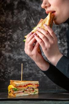 Sanduíche de presunto gostoso de frente sendo comido por uma mulher em uma superfície escura