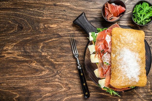 Sanduíche de presunto jamon no pão ciabatta com rúcula e queijo brie de camembert. fundo de madeira. vista do topo. copie o espaço.