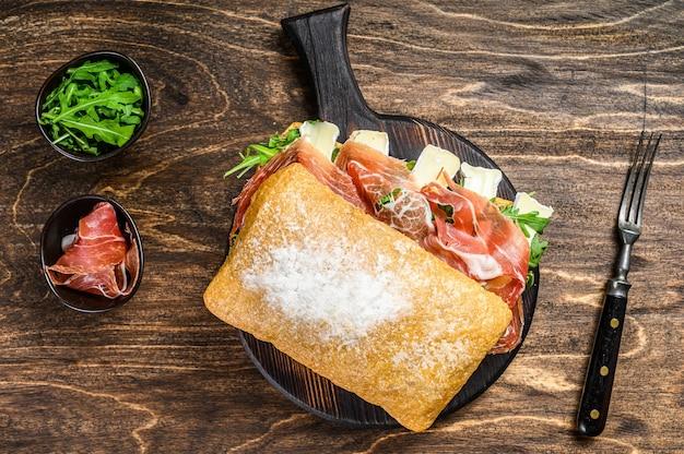 Sanduíche de presunto jamon no pão ciabatta com rúcula e queijo brie de camembert. fundo de madeira. vista do topo.