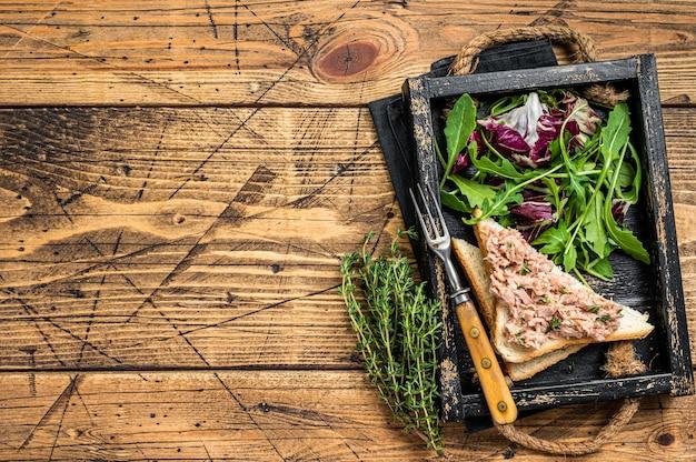 Sanduíche de salada de atum com queijo, alface e rúcula. fundo de madeira. vista do topo. copie o espaço.