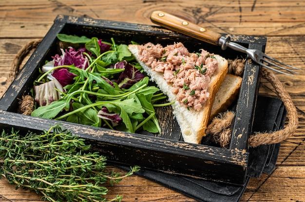 Sanduíche de salada de atum com queijo, alface e rúcula. fundo de madeira. vista do topo.