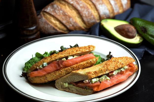 Sanduíche de salmão defumado com abacate em molho servido no pão com gergelim