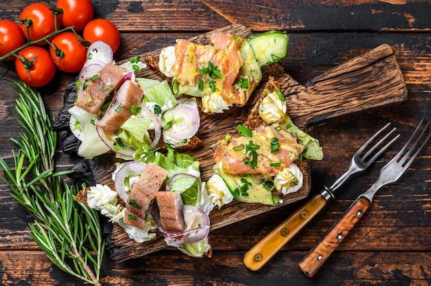 Sanduíche de salmão defumado com arenque com cream cheese e salada em uma tábua de cortar. fundo de madeira escuro. vista do topo.