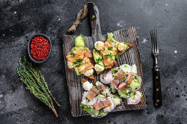 Sanduíche de salmão defumado com arenque com cream cheese e salada. fundo preto. vista do topo.