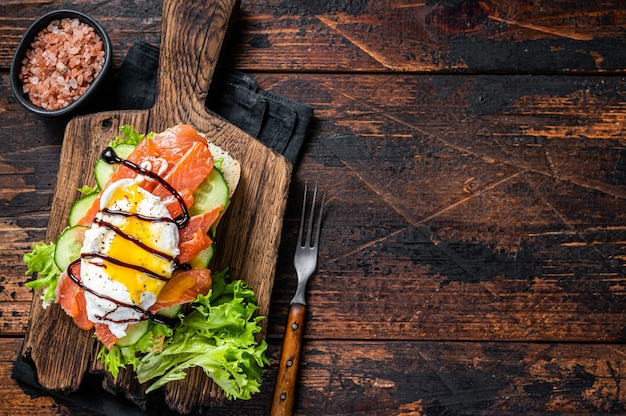 Sanduíche de salmão defumado com ovo benedict e abacate no pão. fundo de madeira escuro. vista do topo. copie o espaço.