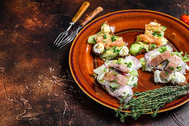 Sanduíche de torrada aberta com salmão e arenque, cream cheese e salada. fundo escuro. vista do topo. copie o espaço.