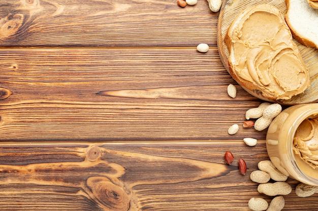 Sanduíche de torrada com manteiga de amendoim. colher e pote de manteiga de amendoim e amendoim para cozinhar o café da manhã em um fundo de madeira marrom. pasta cremosa de amendoim plana com lugar para texto.