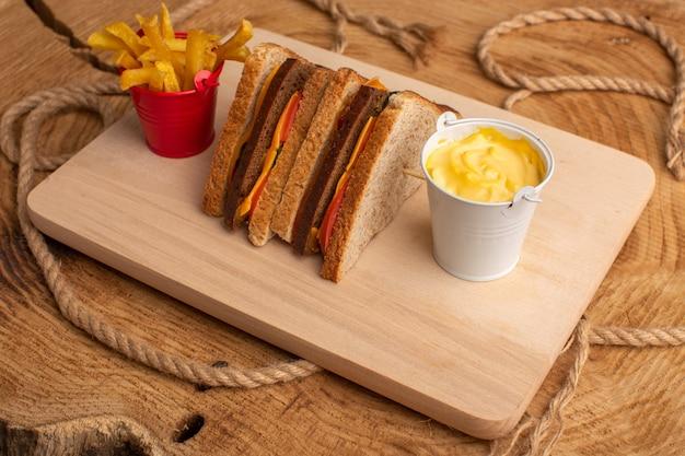 Sanduíche de torrada saborosa com queijo e presunto e batata frita com creme de leite em madeira