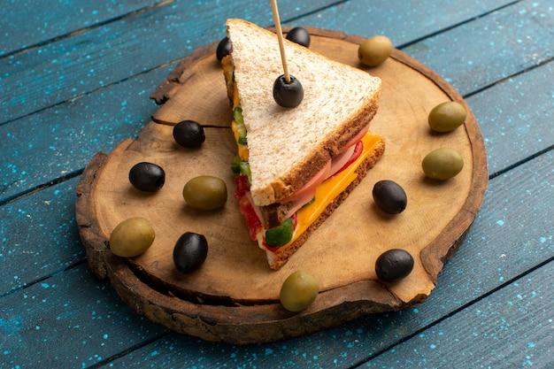 Sanduíche de torrada saborosa de frente com presunto de queijo e azeitonas em madeira azul