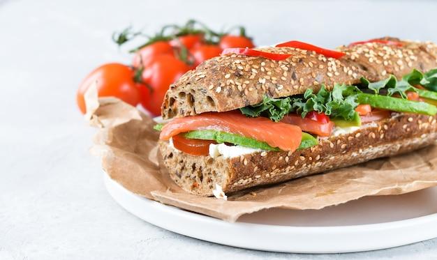 Sanduíche de uma baguete de cereais com abacate, salmão, cream cheese, tomate e alface