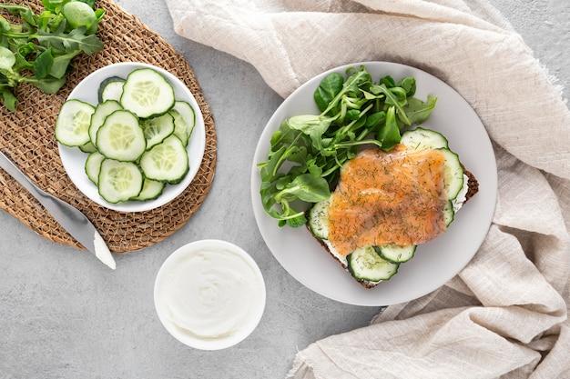 Sanduíche de vista de cima com pepino e salmão no prato com espinafre