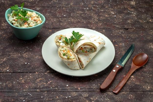 Sanduíche de vista frontal fatiado com salada e carne dentro, junto com salada maionese prato branco sobre marrom